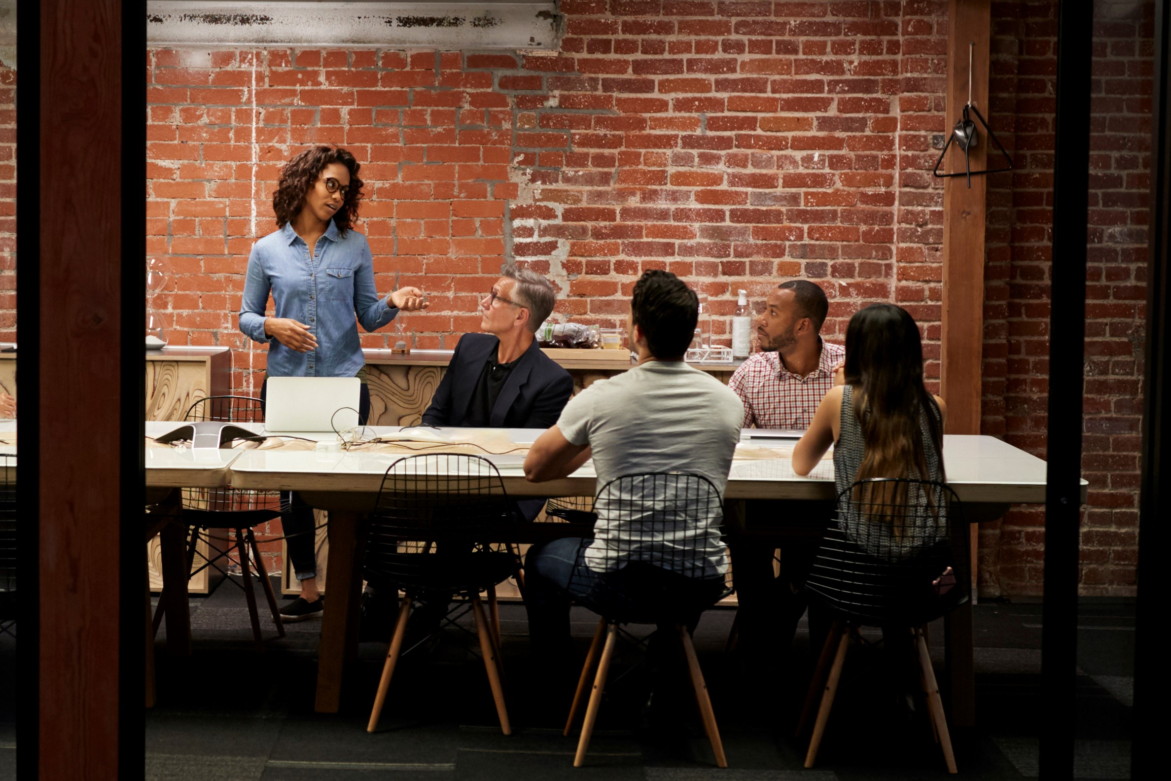 Canva - Business Team Having Late Night Meeting Sitting around Boardroom